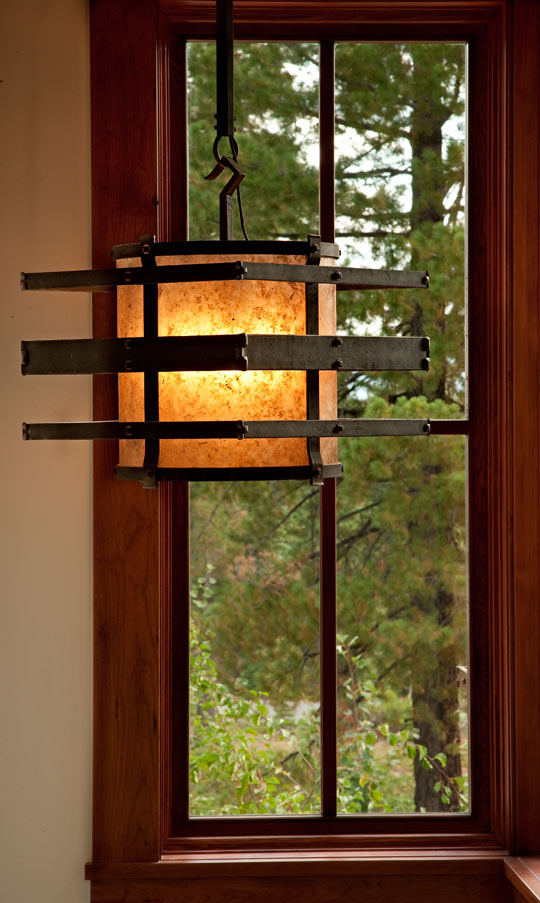 A stairway light that plays off window and trees